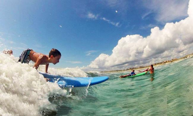 Students at a surf camp learning how to ride a wave in St. Augustine, Florida.