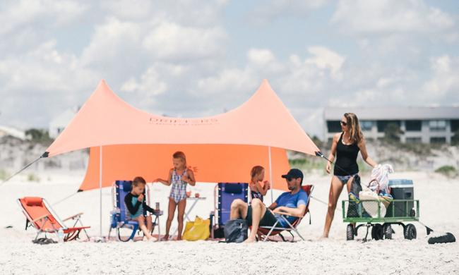A family enjoys the beach under a shaded canopy with chairs, toys, a wagon to tote supplies, and a cooler.