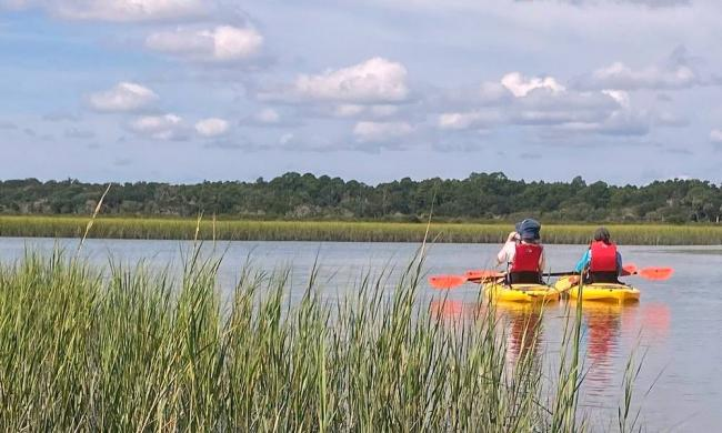 Two people on a Geo Trippin' Kayak tour from Genung's explore the marshes and oyster beds of the Matanzas.