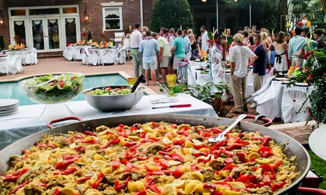 A large dish of paella at an outdoor party.