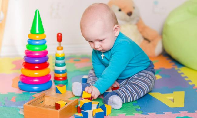 Infant playing with blocks and other toys