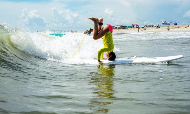 boy headstanding on surfboard