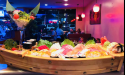 A Sushi Boat and the interior of Baitong Thai Sushi Restaurant in St. Augustine.