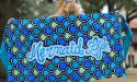 Mermaid Life towel with fin scales pattern on it in blue, teal, and green.
