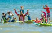A group of surfers and instructors in the water, smiling and posing in St. Augustine, FL.