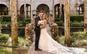 A bridal couple posting for photos on the bridge in the garden of the Lightner Building in St. Augustine.