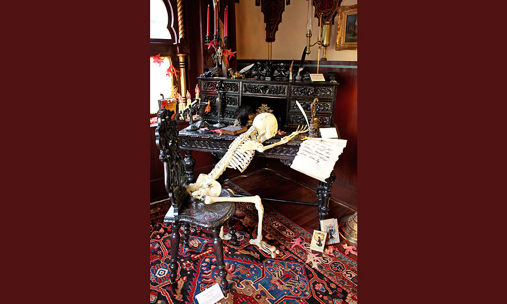 a skeleton sits at a desk in the victorian halloween exhibit at villa zorayda - Victorian Halloween Decorations
